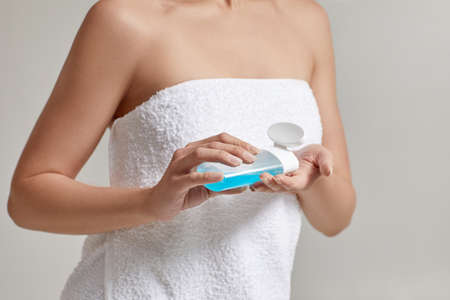 womens hands hold tonic to remove makeup. skin cleansing Banco de Imagens