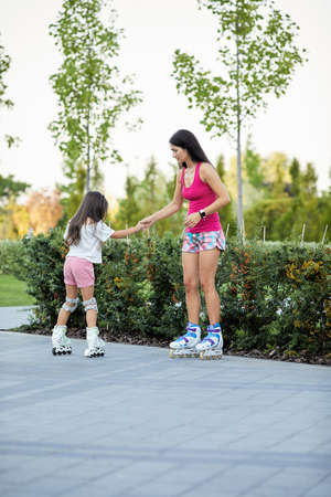 Young mother and her little daughter rollerskating in park Banco de Imagens - 155859739