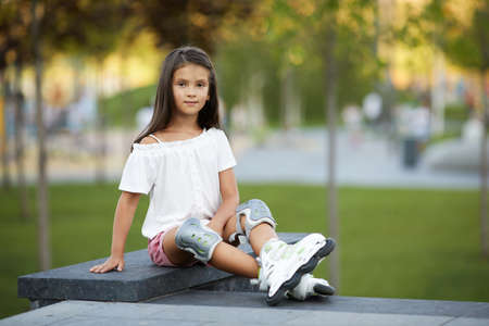 happy cute little child girl in roller skates loooking at the camera in summer park.