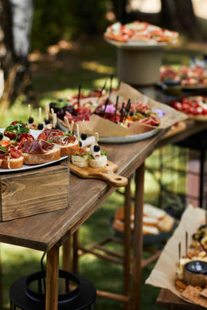 wooden buffet table with snack, appetizer and fruits decorated outdoor in summer day Banco de Imagens - 155870769