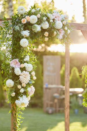Arch for the wedding ceremony decorated with flowers in sunny summer day Banco de Imagens - 156075772