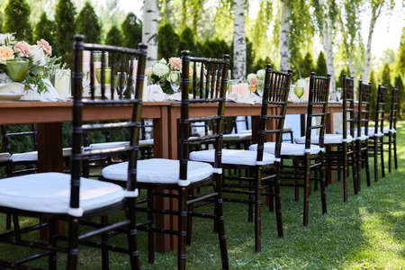 chairs and dinner tables with white cloth, served with porcelain and green glasses. Georgeous wedding table decorated with flowers on a green lawn