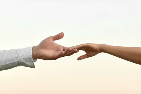 man and woman hand touch each other. couple holding together on sky background Banco de Imagens - 156075640