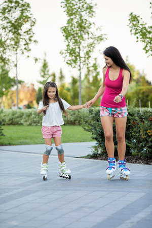 beautiful mother and her little daughter rollerskating in park Banco de Imagens - 156075668