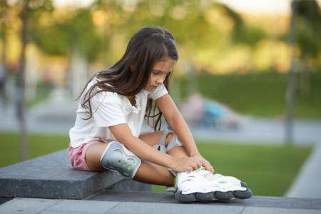 happy little child girl is wearing roller skates while sitting in summer park. Banco de Imagens - 156193811