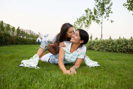 happy mother and daughter in roller skates are sitting on grass and having fun in park. little girl is kissing her mother Banco de Imagens - 156193812