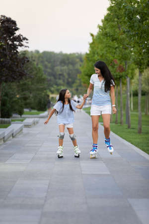 happy mother and her little daughter rollerskating in summer park. family have fun Banco de Imagens - 156193813