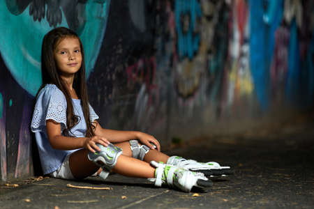happy tired little child girl in roller skates is resting after rollerskating in park in the evening Banco de Imagens - 156193815