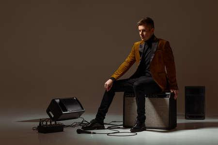 handsone singer in suit sitting on a musical column in the studio dark background Banco de Imagens