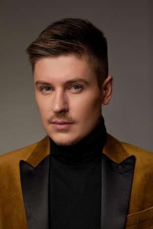 portrait of handsone man in brown suit on dark background