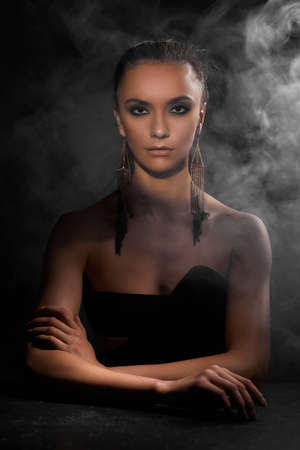 portrait of beautiful sexy brunette woman in fashionable earrings looking at the camera on dark background with smoke Banco de Imagens - 156193821