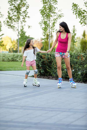 Young mother and her little daughter rollerskating in park. family having fun outdoor
