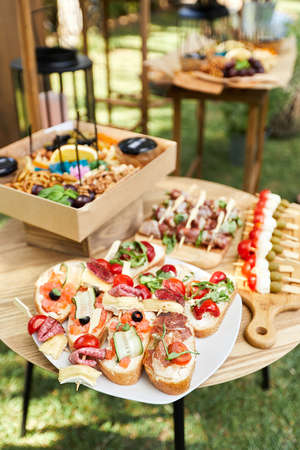 wooden buffet table with snack, appetizer and fruits decorated outdoor in summer day Banco de Imagens - 156130077