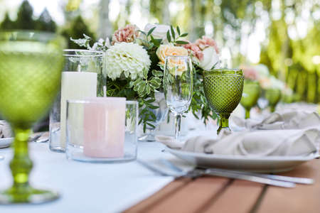 dinner tables with white cloth, served with porcelain and green glasses. Georgeous wedding table decorated with flowers Banco de Imagens - 156130042