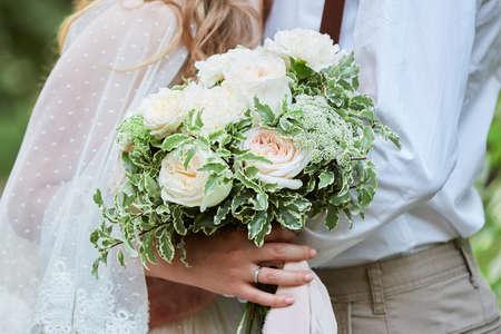 Elegant bride and groom are holding white wedding flowers bouquet outdoor Banco de Imagens - 156159656