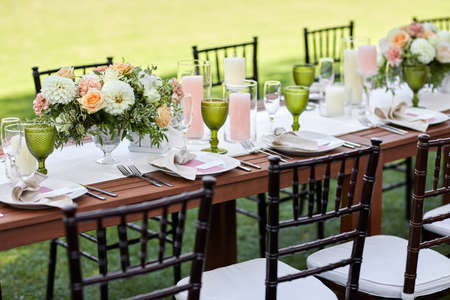 dinner tables with white cloth, served with porcelain and green glasses. Georgeous wedding table decorated with flowers Banco de Imagens - 156161734