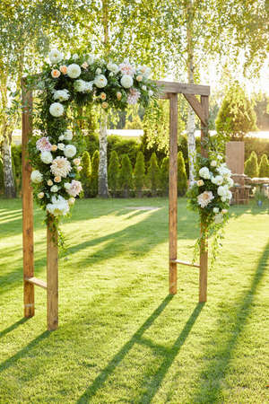 Arch for the wedding ceremony decorated with flowers in sunny summer day. rustic wedding ceremon