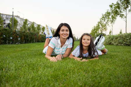 mother and daughter in roller skates are sitting on grass and looking at the camera in summer park. Banco de Imagens - 156162062