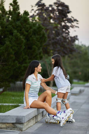 happy little child girl and her mother are wearing roller skates while sitting in summer park.