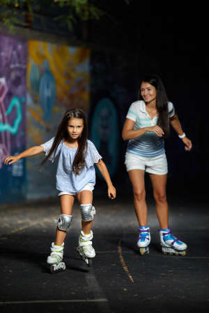 young mother and her little daughter rollerskating in the evening. family have fun
