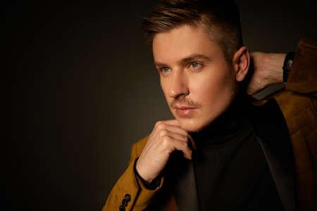 fashion portrait of handsone sexy man in autumn suit on dark background. copy space