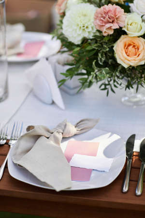 place cards for with the guests name on the plate. dinner tables with white cloth, served with porcelain and decorated with flowers Banco de Imagens