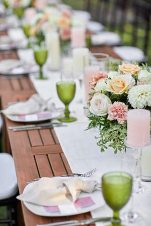 dinner tables with white cloth, served with porcelain and green glasses. Georgeous wedding table decorated with flowers Banco de Imagens - 156205884
