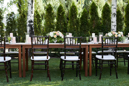 chairs and dinner tables with white cloth, served with porcelain and green glasses. Georgeous wedding or event party table decorated with flowers on a green lawn Banco de Imagens