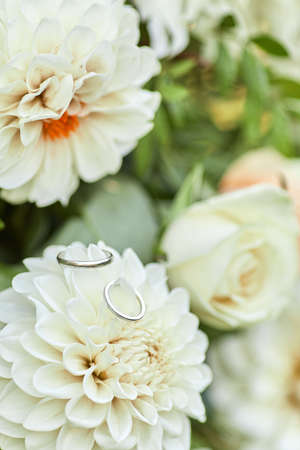 two wedding rings and beautiful flower bouquet, close-up
