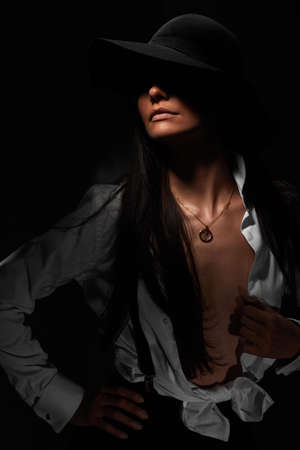 portrait of beautiful sexy brunette woman in white shirt and black hat on dark background
