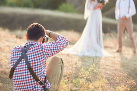 professional photographer takes pictures of the bride and groom in nature on the sunset, wedding photographer in action Standard-Bild