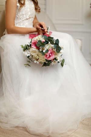 bride holding the beautiful wedding bouquet in studio interior
