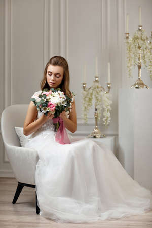 beautiful tender young bride with flower bouquet sitting on armchair in white studio interior