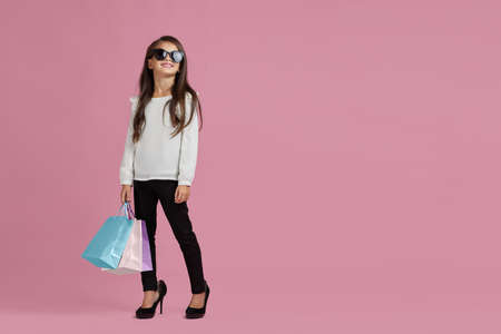 sale. fashionable cute little child girl in sunglasses and oversized mothers shoes is holding shopping bags on pink background. copy space for text