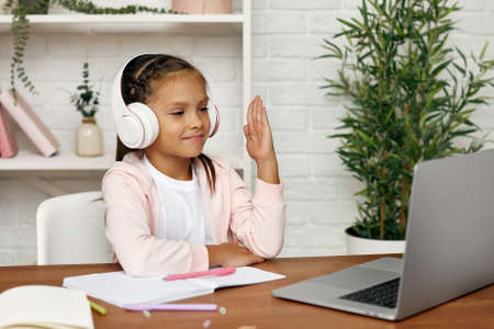 smiling little child girl using laptop for studying online. child raises her hand to answer the teachers question. online lesson at home