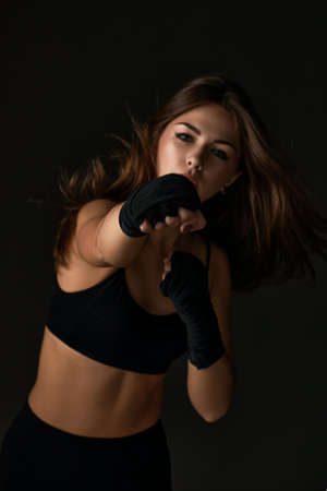 sporty woman with boxing bandages punching on black background. Focus on hand