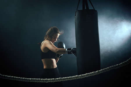 sporty brunette woman in boxing gloves and sportswear hitting the boxing bag in dark background with smoke.