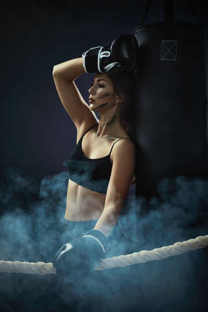 sporty woman in black boxing gloves leaning on punching bag in dark background. woman resting after workout