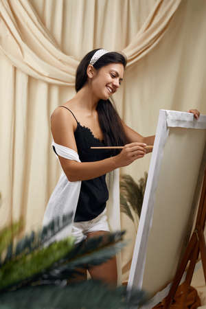 Young smiling female artist in front of easel. Woman painting in art studio Banco de Imagens