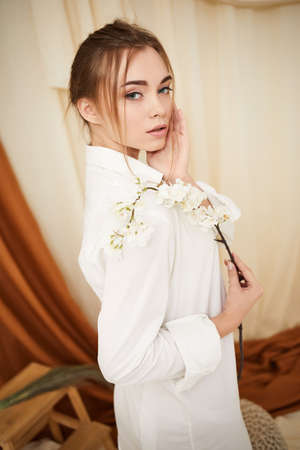Fashion art photo of young gorgeous woman with white flower in studio interior. soft light Banco de Imagens