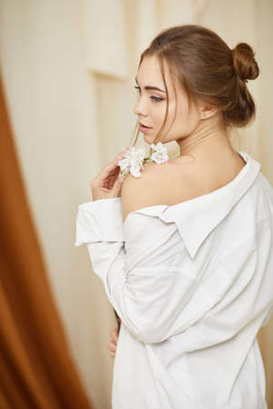 Fashion art photo of young sensual woman with white flower in studio interior. soft light. female tenderness and beauty