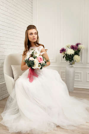 gorgeous beautiful young bride in a luxurious wedding dress with flower bouquet in white studio interior, full lenth Archivio Fotografico