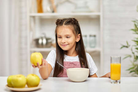 cute little child girl having breakfast - cereal, orange juice and apple in the kitchen. healthy breakfast