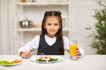 little child girl having breakfast - fried egg and orange juice in the kitchen. healthy breakfast. fried egg face smiles on a white plate Banco de Imagens