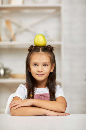 little child girl sitting at the table with apple on head in the kitchen.