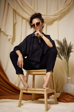 Fashion art photo of beautiful brunette woman in sunglasses, black shirt and trousers in studio interior. soft light Banco de Imagens