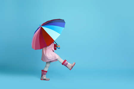 funny little child girl with multicolored umbrella in pink rain coat and rubber boots on blue background. copy space
