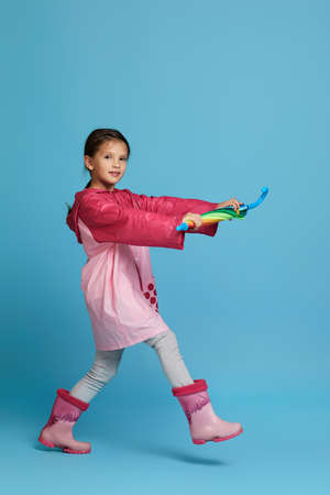 happy funny child girl with multicolored umbrella in pink rain coat and rubber boots on blue background.