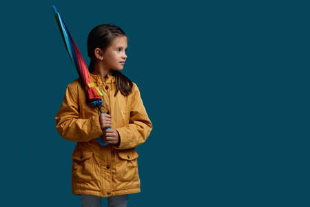 cute child girl with multicolored umbrella in yellow rain coat on blue background. autumn mood. copy space