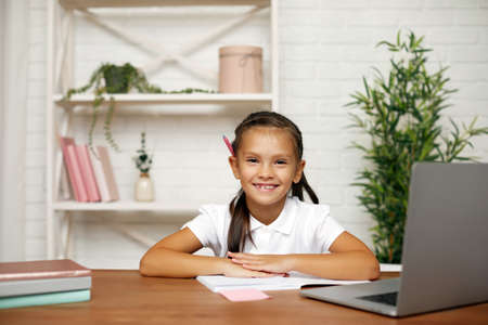 smiling little child girl using laptop for studying online learning system. online lesson at home